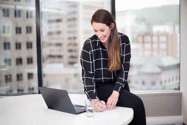 Un membre de l'équipe qui lis sur son ordinateur et qui prend des notes