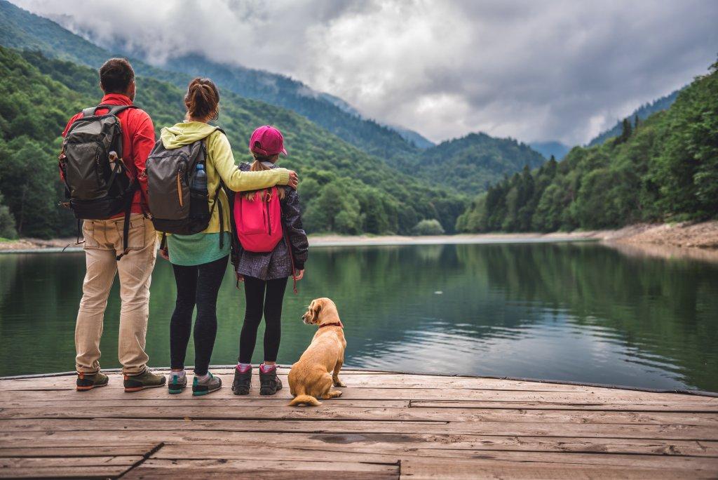 Une famille et leur chien sur le bord d'un lac